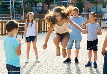 Happy children skipping on jumping elastic rope