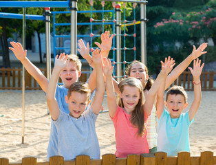 Cheerful kids posing  and hands up