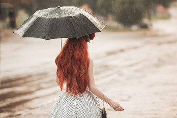Wet weather. Autumn rain. Unhappy girl in polka dots dress hold  black umbrella. Raining in city. Wet umbrella against the backdrop of the street. Woman was caught in the rain. Alone unhappy girl