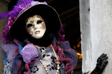 Carnival lilac-black mask and costume at the traditional festival in Venice, Italy