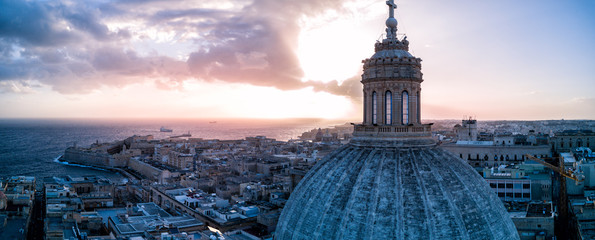 Aerial drone sunrise photo over Our Lady of Mount Carmel basilica.  A domed cathedral that overlooks the ancient capital city of Valletta, Malta.  Island country in the Mediterranean Sea.