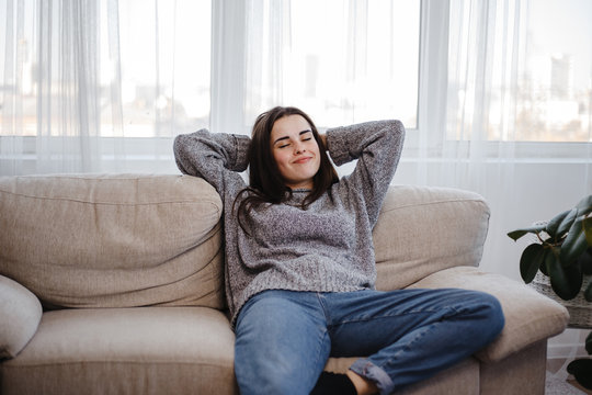 Young woman relaxing on a couch in living room. Home, comfort, dreaming and harmony