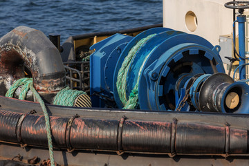 Detail of a powerful towing winch: the reel is equipped with thousands of meters of powerful power cable and end connection. Mooring winches on deck for container vessel, front mooring ropes winches