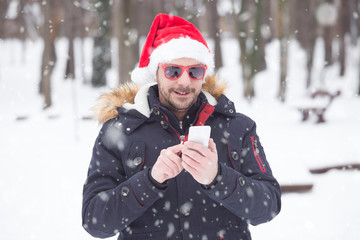 Portrait of young man with santa hat and sunglasses on snow day sending sms