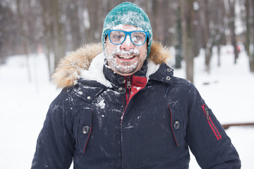 Portrait of male face covered with snow. Crazy, cheerful, funny, comic and emotions . Winter concept
