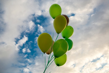 green balloons on blue sky with clouds of background