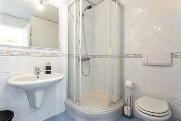 Modern toilet bathroom with shower inside in hotel.