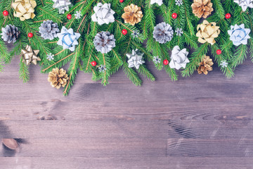 On a wooden dark background, a Christmas composition of fir branches, cones and bows. Copy space.