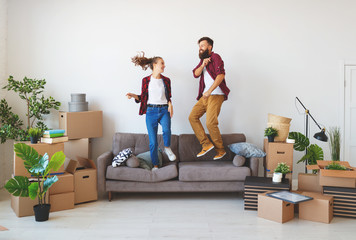 happy young married couple moves to new apartment and laughing,  jump, fight pillows.