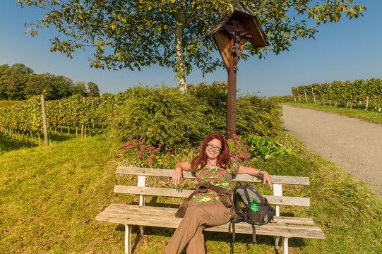 Wanderin Bestager macht Pause auf einer Bank in den Weinbergen