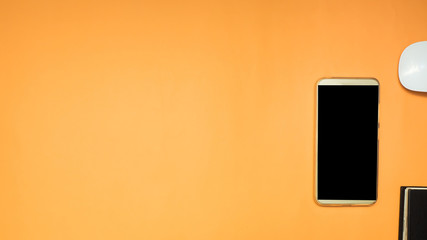 Wall Mural - smartphone and notebook on orange background business concept