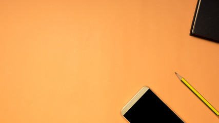 Wall Mural - smartphone and pencil on orange background business concept