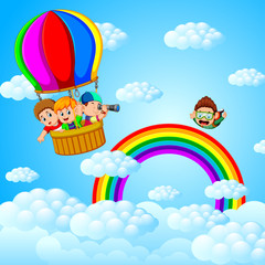 Poster Regenboog happy kids flying in a hot air balloon and skydiver