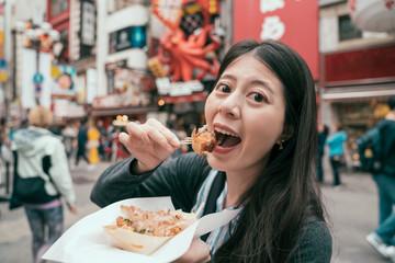 traveler eating takoyaki on the teeming street