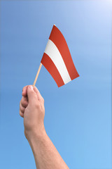 Hand holding Austria flag high in the air, with a clear blue sky