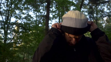 1c3f7858b04 0 13 Slow motion video of a handsome man putting on a warm beanie hat in a  forest