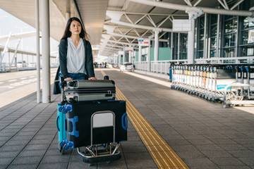 woman outside international airport with trolley