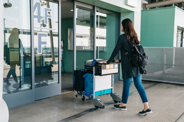asian girl carrying luggage entering airport