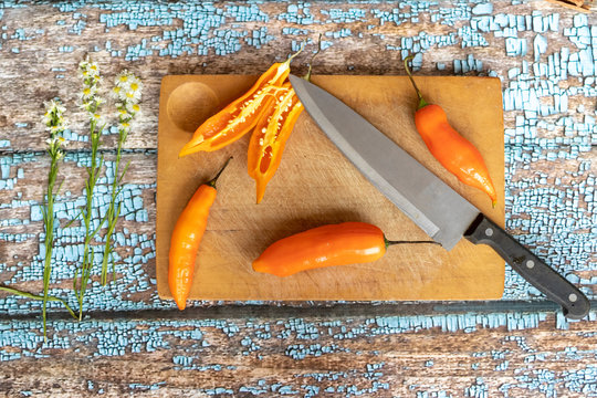 Several ajies being chopped by knife on a kitchen board