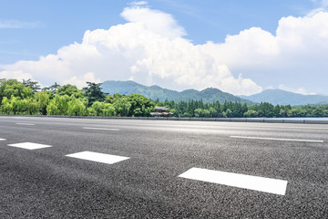 Asphalt road and green mountain under the blue sky
