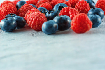 Blueberries and raspberries mix on the background of gray cement. Ripe and juicy fresh raspberries and blueberries close-up. A lot of berries close-up.