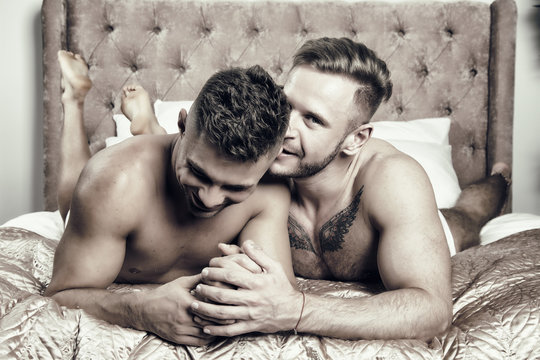 Two attractive guys relaxing on the bed.