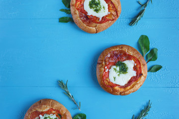 Homemade Mini Pizza with Tomatoes, Cheese and Bacon, Injuries and Spices on Light Blue Background