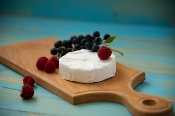 cheese camembert with raspberries and grapes on a table