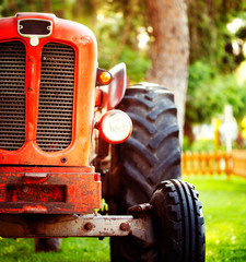 Wall Mural - Croppped photo of old vintage red tractor standing on a farm field at sunset.