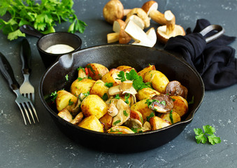 Baked potatoes with mushrooms in a frying pan.