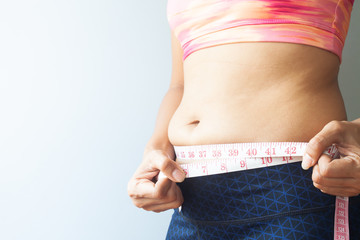 Slimming woman with belly fat, Sporty woman measuring belly fat. Close up