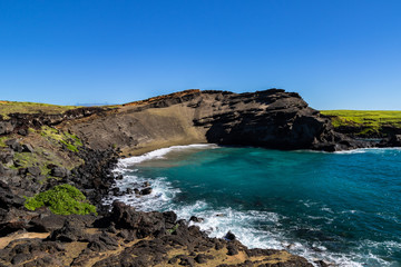 Green sand beach (papakolea) near South Point on Hawaii's Big Island. Beach is at the bottom of the steep slope; blue-green ocean, rocky shoreline is in the foregound.