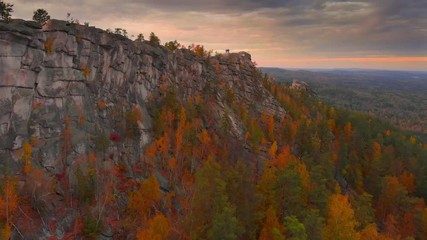 Wall Mural - Autumn landscape: scenic cliffs covered by colorful forest, epic sunset in background. Aerial view 4K UHD
