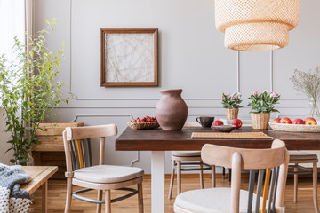 Vintage wooden chairs in living room with long table with strawberries, apples, vase and flowers on it, real photo