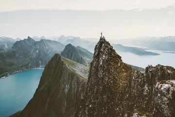 Man climber standing on cliff mountain edge above fjord in Norway travel adventure extreme lifestyle journey vacations solitude emotions mountains landscape Wall mural