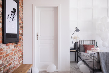 White entrance door to stylish bedroom interior with brick wall and bed with birthday cake and balloons, real photo with copy space