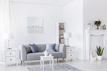 Table on carpet in front of grey settee in white living room interior with lamps and poster. Real photo
