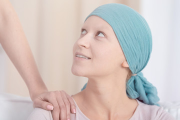 Woman with cancer wearing headscarf looking up at someone