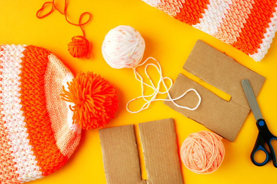Knitting warm hat with a pompon. View from above. Knitting warm clothes for autumn and winter. Make pompom for a knitted cap. Yarn on a yellow background.