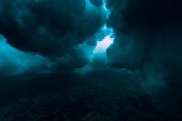 Wave underwater with bubbles. Deep underwater