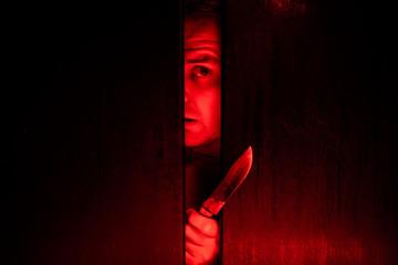 Serial killer / eye peeking behind the door with kinfe - fototapety na wymiar