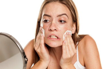 young beautiful girl cleaning her face with cotton pads on white backgeound