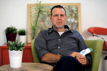 Omri Ofer, CEO of Israeli company ParaSonic, poses for a picture as he holds a prototype of the company's hand-held device that kills lice and their eggs, in Tel Aviv
