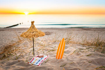 Beach Life Sunset / Beach holiday lifestyle miniatures (straw sunshade, surfboard, towel, book) at beautiful sunset background (copy space)