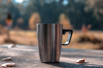 A cup of tee standing on a outdoor desk in a beautidul autumn scenery. coffee, tee, fall, landscape, cup, outdoor drink;