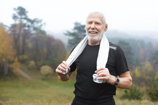 Happy elderly Caucasian male with stubble choosing active lifstyle, smiling broadly after intensive morning cardio workout in park, wiping sweat using white towel. Health, well being and energy