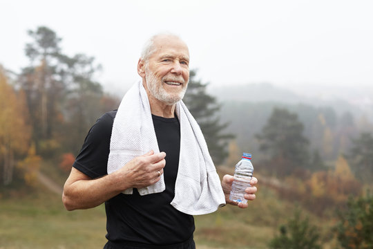 Exhausted elderly male with gray hair and beard drinking water after outdoor exercise and wiping sweat with towel around his neck. Tired but happy old senior man resting after running workout