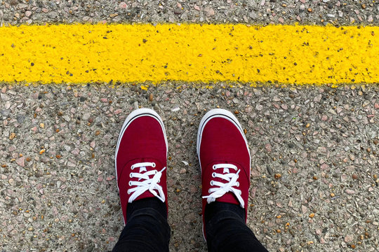 Red sneakers in front of the yellow line. Safety concept