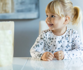 Little blonde toddler girl sitting at kitchen table and smiling to someone