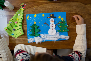 Top view of child, doing snowman and winter tree. Scissors, glue stick, pencil, markers, paper sheets and scraps on wooden background.